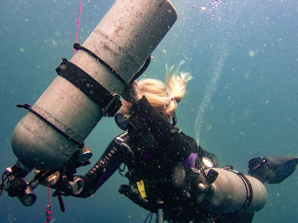 Sidemount diver cleaning up tank